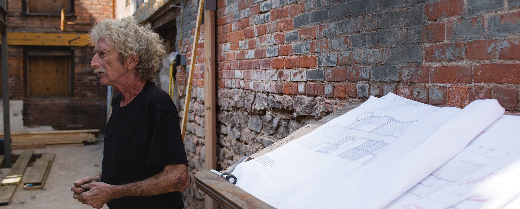 Joel Landy poses near architectural plans.