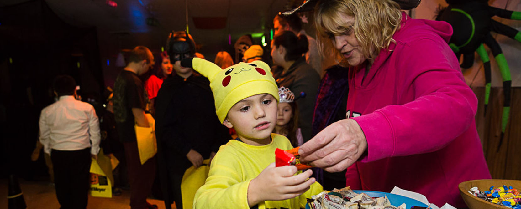 A woman and two children in costume at a Halloween Party
