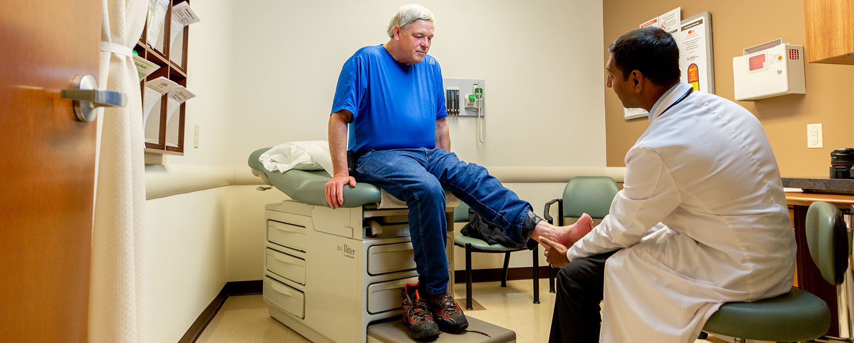 Older adult patient receives a foot exam by a doctor.