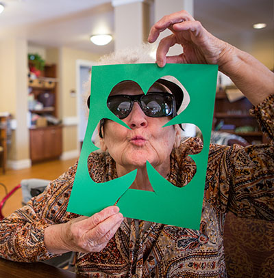 Older adult woman makes funny face through cutout of shamrock