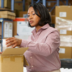 Cooperative worker packs merchandise into a box